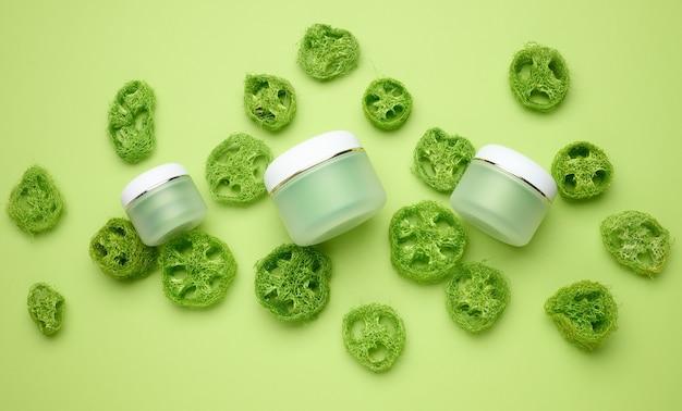 Pot blanc vide pour les cosmétiques sur fond vert. emballage pour crème, gel, sérum, publicité et promotion de produits. maquette, vue de dessus