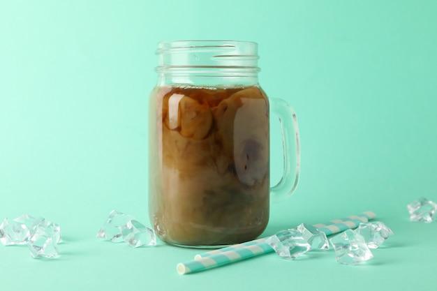 Pot de café glacé, glaçons et pailles sur fond de menthe