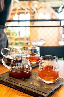 Pot de café noir goutte froide avec verre et glace dans un café et un restaurant