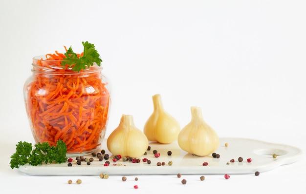 Pot de carottes fermentées à côté d'ail mariné isolé sur fond blanc avec copie espace