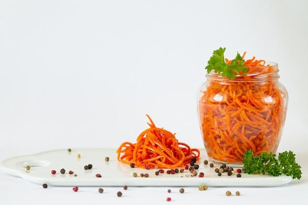 Pot de carottes fermentées isolé sur fond blanc avec espace de copie. concept de légumes conservés
