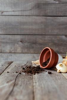 Pot en céramique retourné avec le sol sur une vieille table en bois gris, bulbes de tulipes. photo de haute qualité