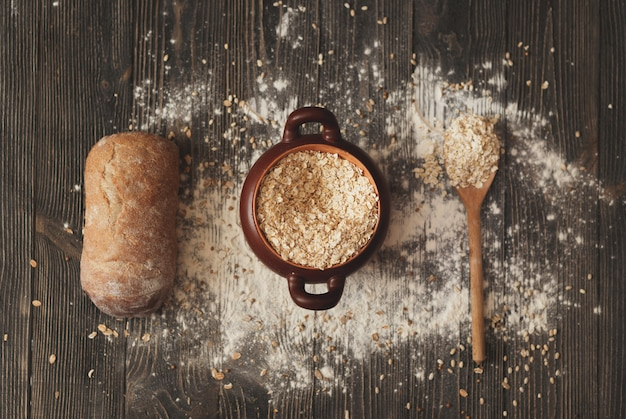 Pot avec des céréales de cuillère et du pain sur fond rustique. vue d'en-haut.