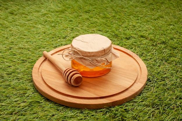 Pot de close-up avec du miel bio sur une planche