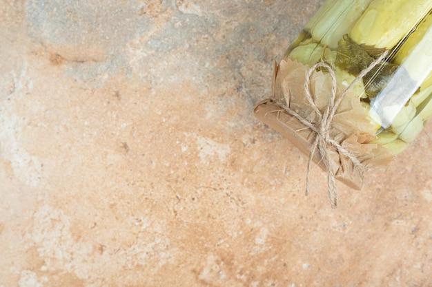 Un pot de concombres marinés maison sur une surface en marbre