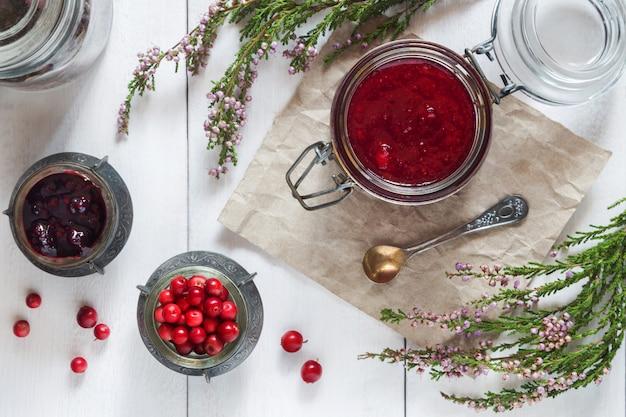 Pot de confiture d'airelle rouge avec des baies sur une table en bois blanc