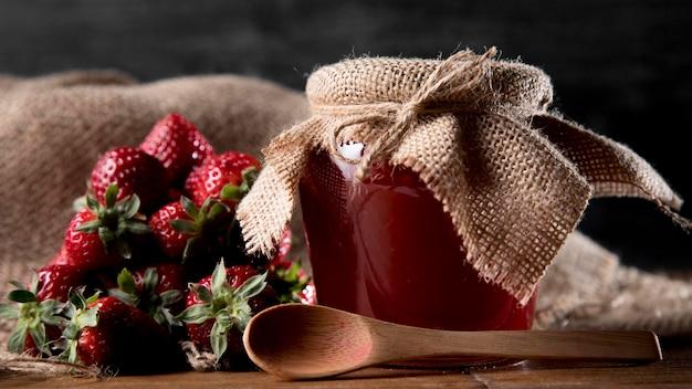 Pot avec confiture de fraises et cuillère
