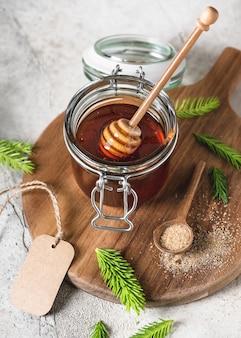 Pot de confiture maison à partir d'aiguilles de jeunes bourgeons de sapin et de sucre nature avec cuillère à miel en bois