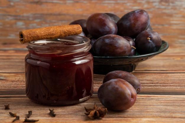 Un pot de confiture avec des prunes autour.
