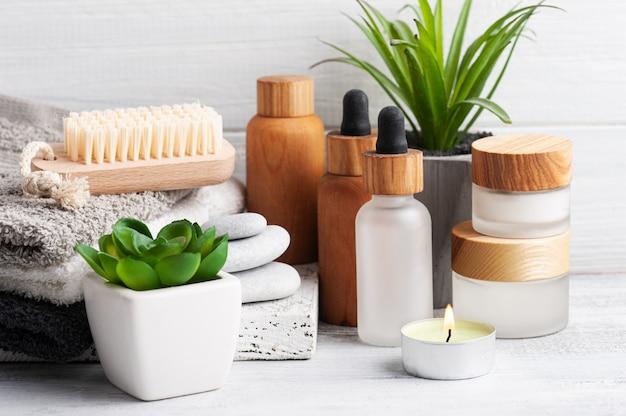 Pot cosmétique avec crème, lotion hydratante pour le corps et huile essentielle sur fond en bois. spa bio naturel avec emballage écologique