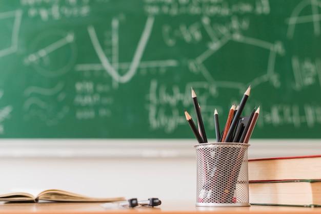 Pot à crayons et livres sur le bureau en classe de mathématiques