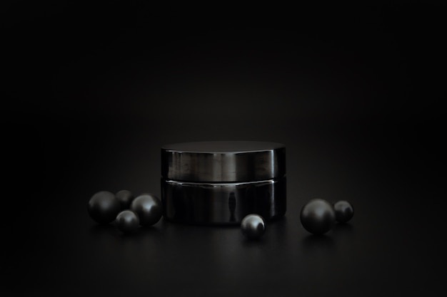 Pot de crème cosmétique sans marque noir. présentation crème sur fond noir. maquette élégante. soin de la peau, produit de beauté.