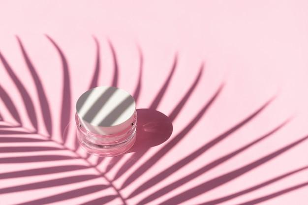 Pot de crème avec ombre de feuille de palmier sur fond rose. concept de traitement de beauté de soins du corps d'été.