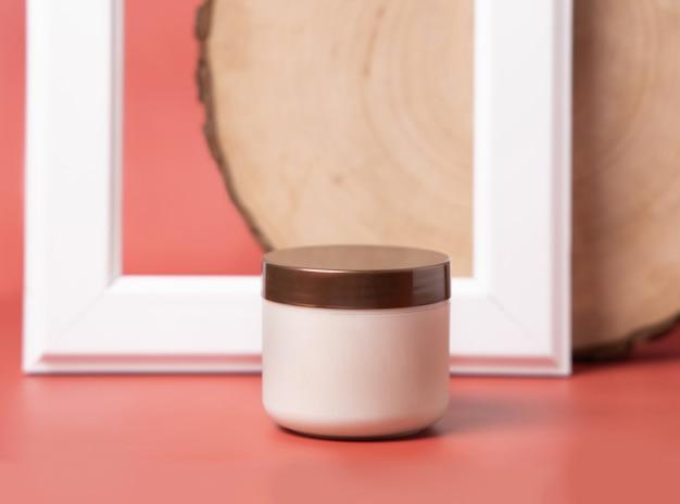 Pot de crème pour le visage, de gommage ou de beurre corporel sur fond rose en gros plan. maquette pour la conception modèle de produit cosmétique. soins de la peau, dermatologie, concept de bien-être. espace pour le texte