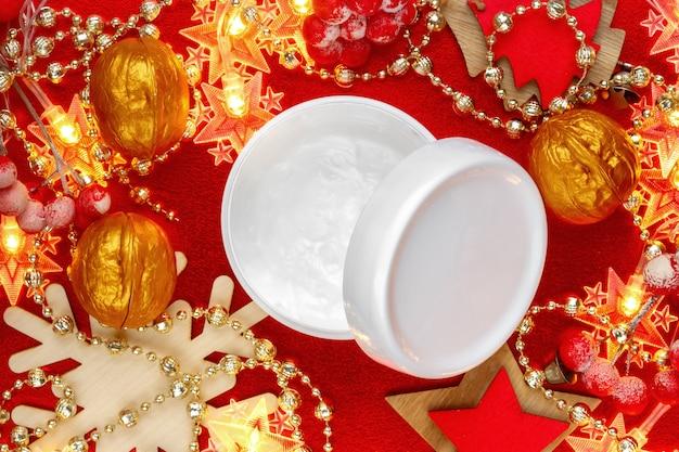 Pot de crème pour le visage naturel sur la vue de dessus de noël festif. présent du nouvel an de la femme.