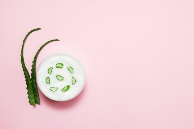 Pot de crème et tranche d'aloe vera sur rose