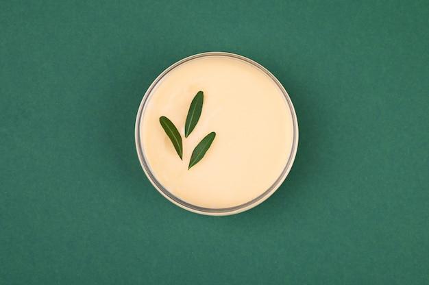 Pot de crème végétale sur fond vert. vue d'en-haut. lieu d'inscription. pot de crème végétale sur fond vert