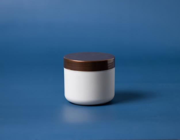 Pot de crème vierge avec couvercle marron sur fond bleu se bouchent. la crème cosmétique peut simuler