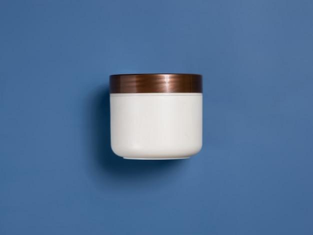 Pot de crème vierge avec couvercle marron sur fond bleu vue de dessus. la crème cosmétique peut simuler