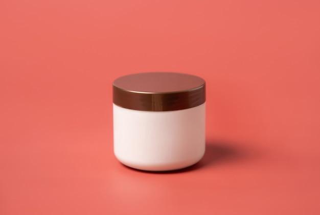 Pot de crème vierge avec couvercle marron sur fond rose se bouchent. la crème cosmétique peut simuler