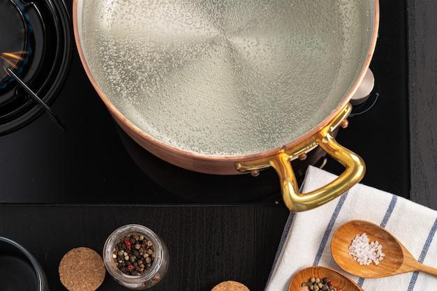 Pot en cuivre avec de l'eau bouillante sur une cuisinière à gaz
