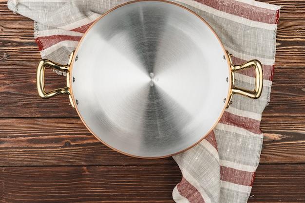 Pot en cuivre avec une nappe de cheker sur une table en bois