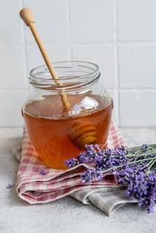 Pot avec du miel et des fleurs de lavande fraîches sur fond de béton