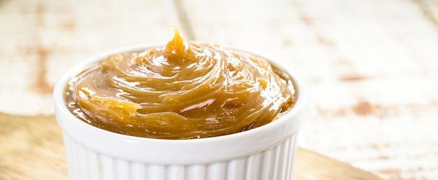 Pot de dulce de leche ou caramel fait maison sur le fond en bois rustique, doux brésilien typique