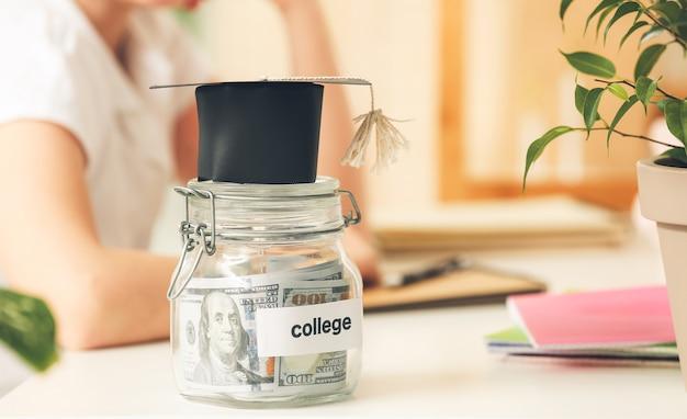 Pot avec des économies pour l'éducation et l'obtention du diplôme sur table de fille à la maison