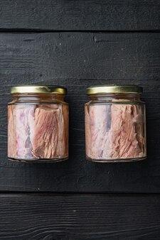 Pot de filet de thon à l'huile d'olive, sur table en bois noir, vue de dessus
