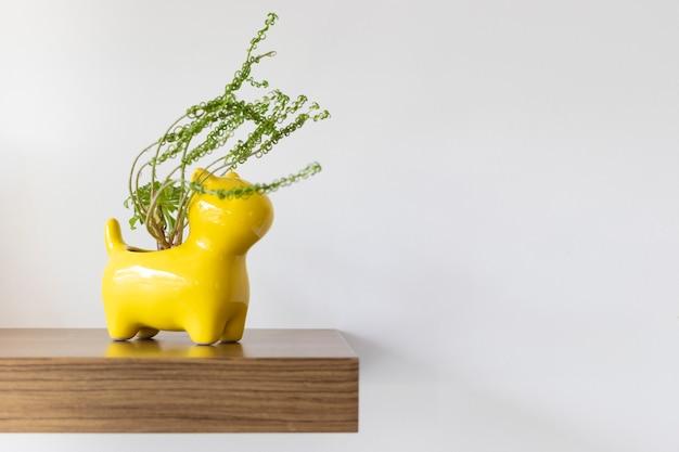 Pot de fleurs jaune en forme de chien avec des plantes
