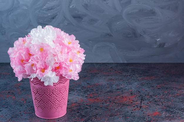 Un pot de fleurs rose rempli de fleurs artificielles roses et blanches.