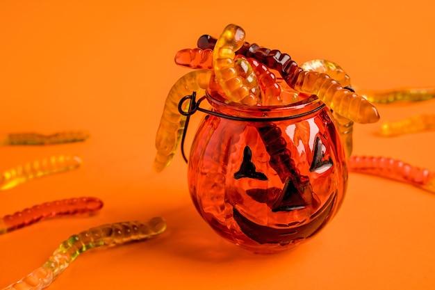 Un pot en forme de citrouille est rempli de vers de marmelade sur un fond orange concept d'halloween