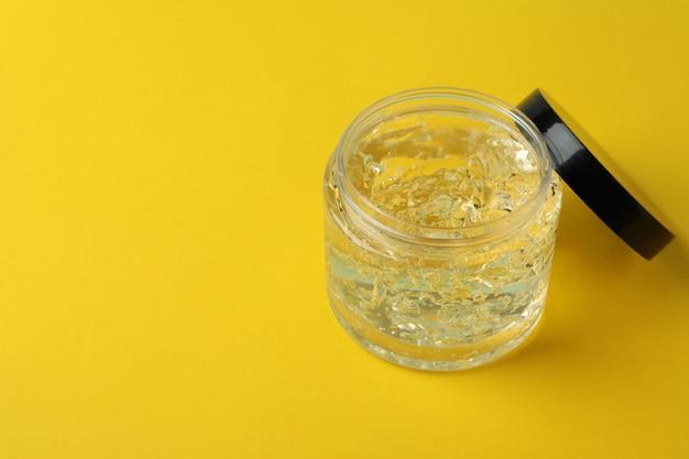 Pot de gel coiffant sur fond jaune, espace pour le texte