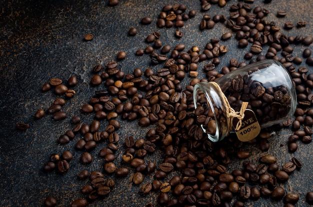 Pot et grains de café saupoudrés sur fond de béton foncé. le concept de boissons chaudes, de production ou de vente de café
