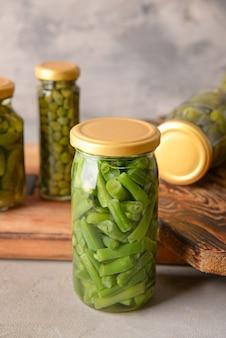 Pot avec haricots verts en conserve sur fond gris