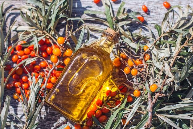Un pot avec de l'huile d'argousier et une branche fraîche d'argousier avec des baies sur un fond en bois