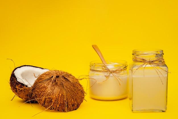 Pot d'huile de noix de coco près de parties de noix de coco sur un fond coloré