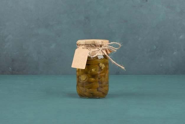 Pot de jalapenos verts marinés et cadre photo sur table bleue.