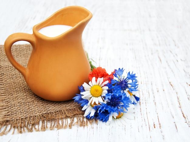 Pot de lait et fleurs sauvages
