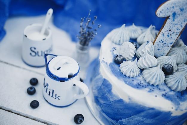 Pot de lait et gâteau sur fond bleu à côté d'un vase avec des branches de lavande
