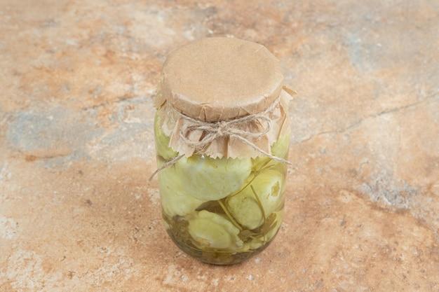 Un pot de légumes marinés sur une surface en marbre