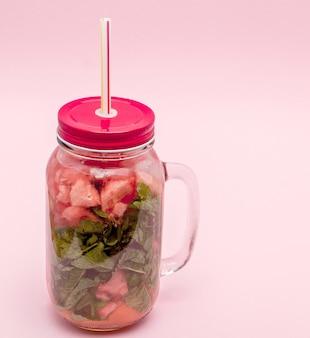 Pot de limonade fraîche froide avec morceau de pastèque et pailles sur mur rose.
