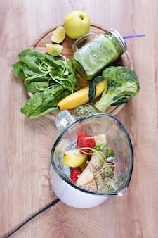 Pot mason de boisson diététique avec brocoli, épinards, microgreens, citron vert et banane et mélangeur plein d'ingrédients sur fond de bois