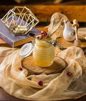 Un pot de mélange de miel cocktail et une écharpe en mousseline.