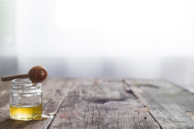 Pot de miel avec un bâton en bois draine le miel sur un vieux fond en bois au-dessus de la fenêtre