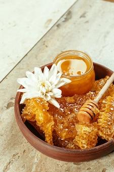 Pot de miel et bâton isolé sur fond blanc