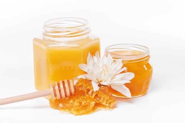 Pot de miel et bâton isolé on white