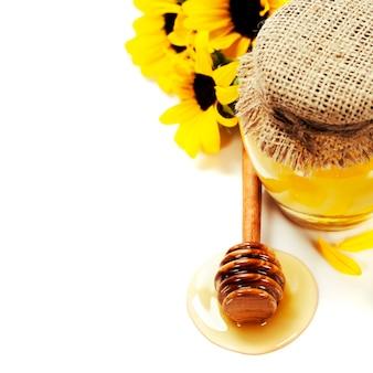 Pot de miel complet et bâton de miel sur blanc et fleurs avec copyspace
