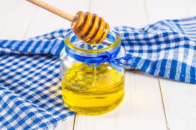 Un pot de miel avec une cuillère, sur une table blanche avec une serviette bleue